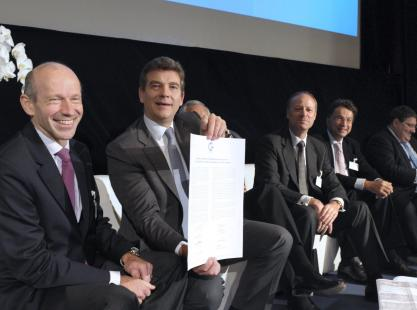 French minister for Industrial Renewal Arnaud Montebourg (2ndL) shows a document signed on stage...